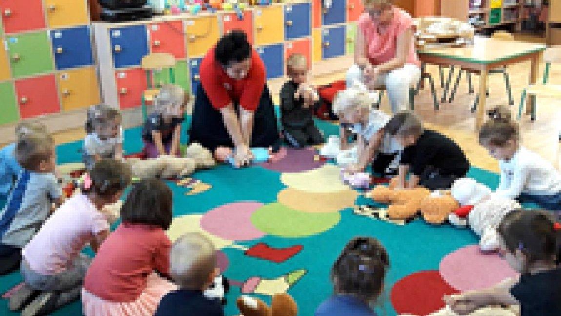 Dzieci siedzące na kolorowym dywanie z dwiema opiekunkami