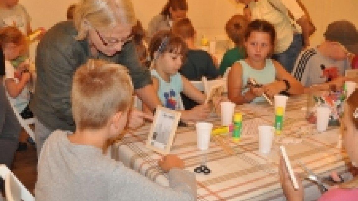 Dzieci wraz z instruktorką podczas warsztatów plastycznych