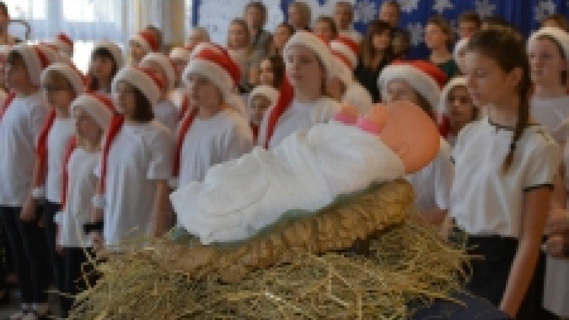 Szkolne jasełka, na pierwszym planie lalka leżąca na sianie, w tle dzieci w czapkach św. Mikołaja