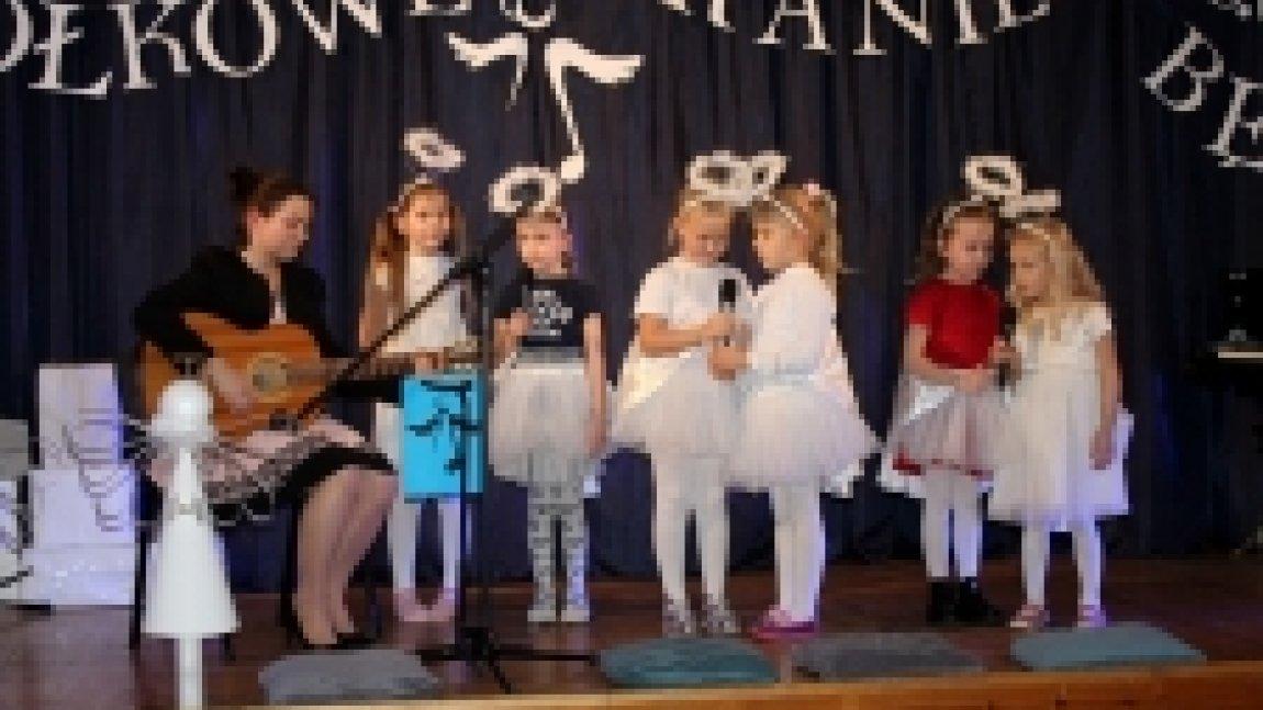 Dzieci na scenie oraz pani grająca na gitarze