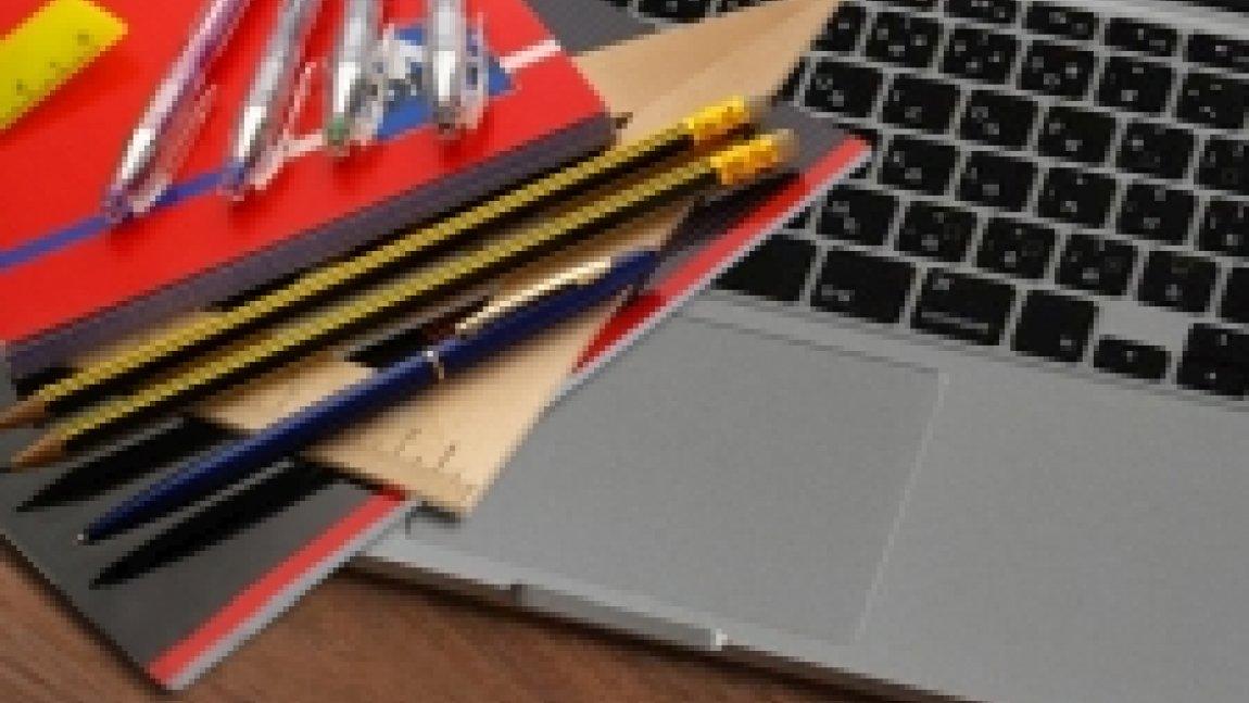 Fragment laptopa, na którym leżą przybory do pisania