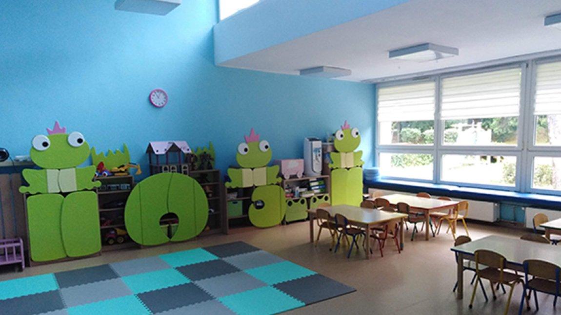 Wnętrze sali przedszkolnej w kolorze niebieskim z seledynowymi meblami