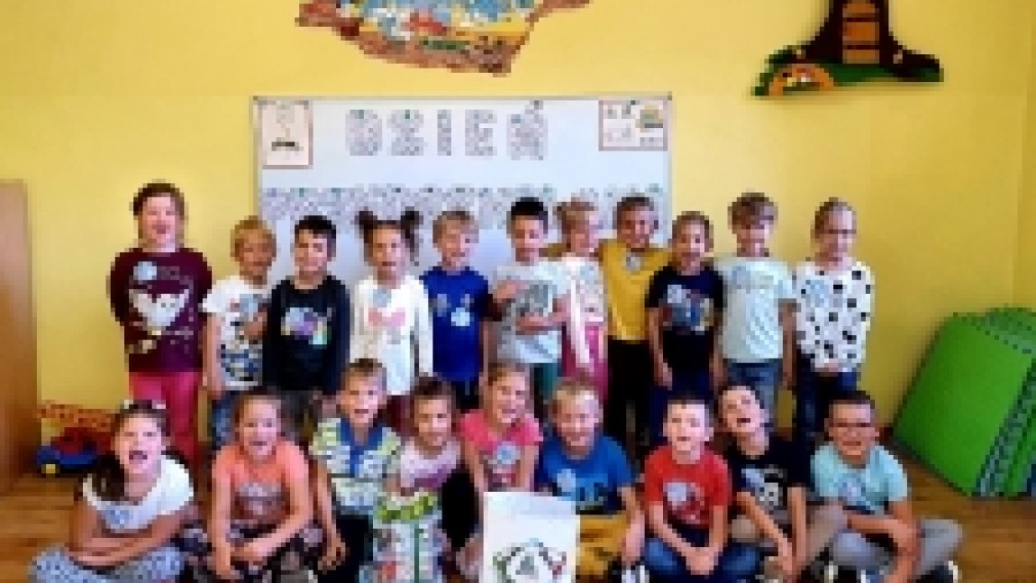Zdjęcie grupowe przedszkolaków na tle żółtej ściany