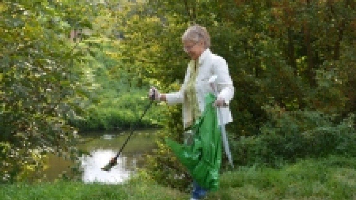 Pani zbierająca śmieci za pomocą chwytaka nad rzeką