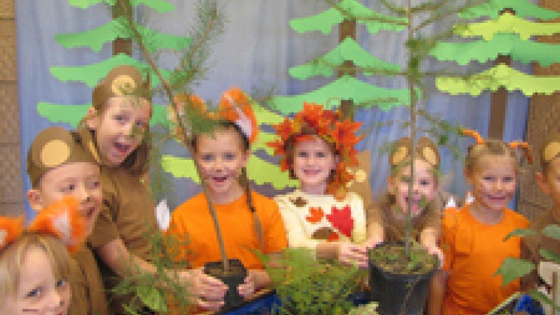 Dzieci trzymające sadzonki drzewek na tle leśnej aranżacji