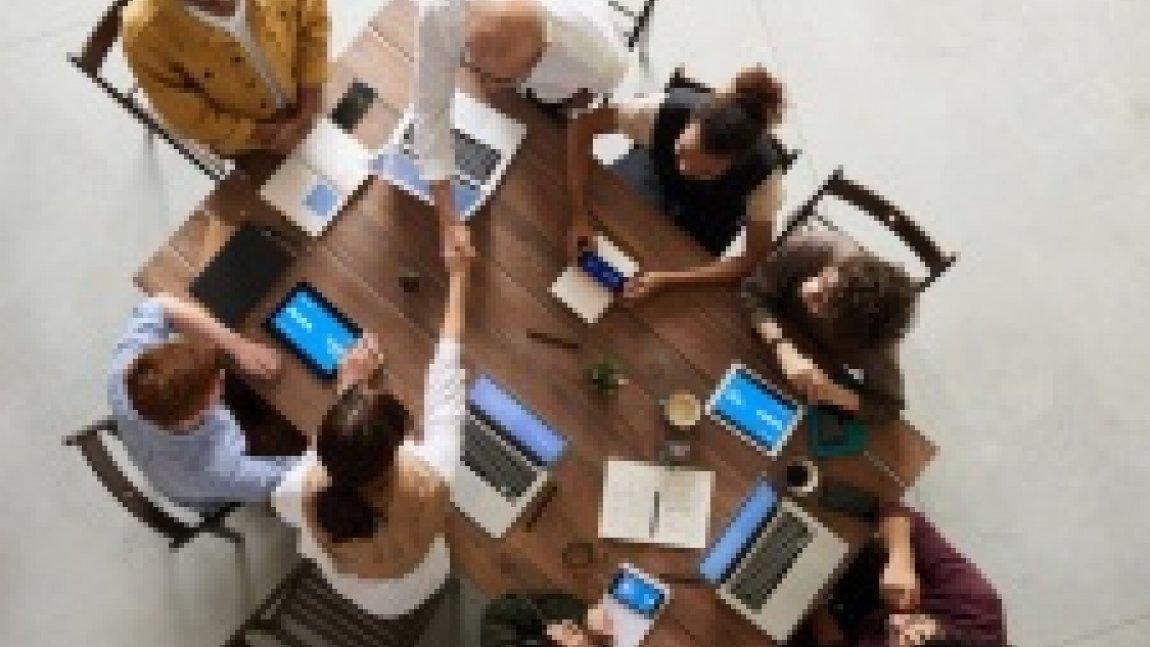 Ilustracja przedstawiająca zdjęcie widziane z góry, osoby siedzące przy stole konferencyjnym