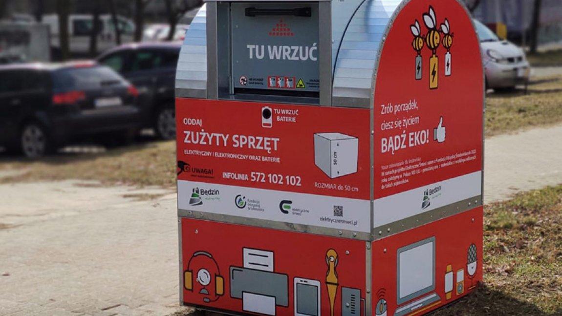 Czerwony pojemnik na elektrośmieci stojący na osiedlu
