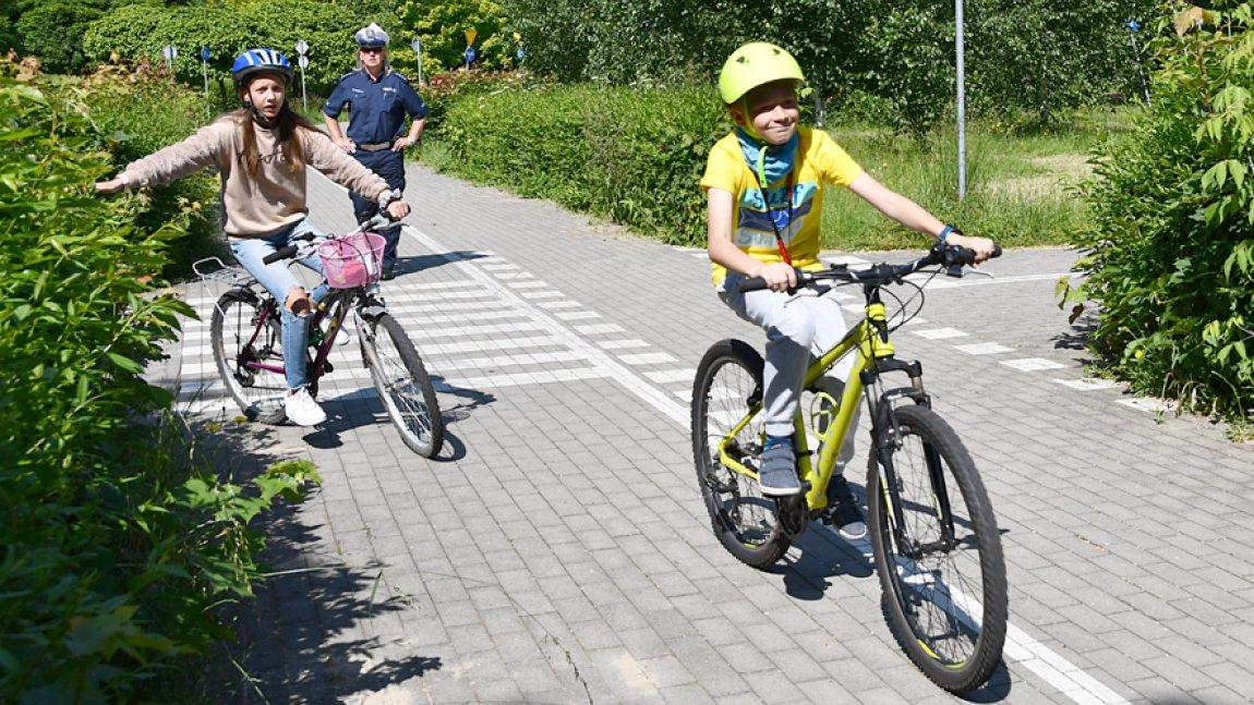 Dzieci jadące na rowerze, w tle funkcjonariuszka Policji