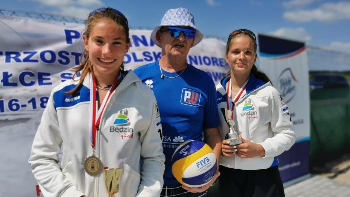 Dwie zawodniczki z trenerem na tle baneru z napisem Połfinał Mistrzostw Polski Juniorek w piłce siatkowej plażowej