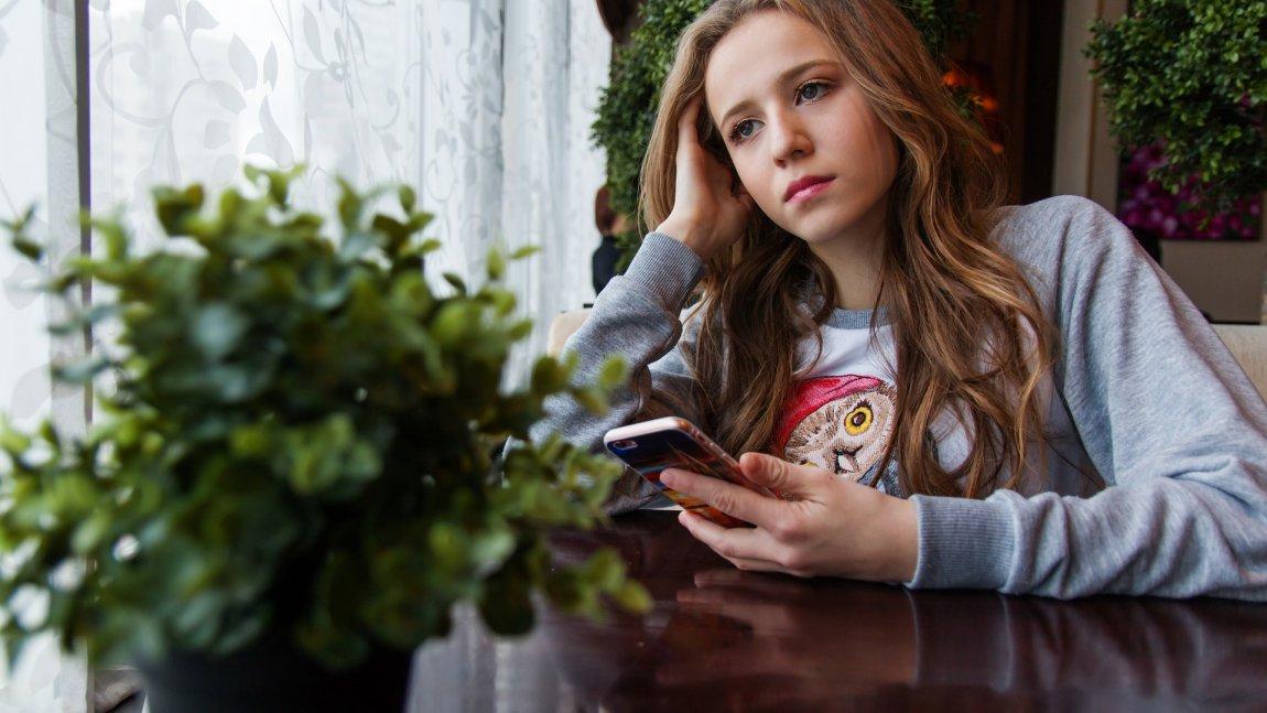 Zdjęcie przedstawiające zamyśloną nastolatkę trzymającą telefon w dłoni