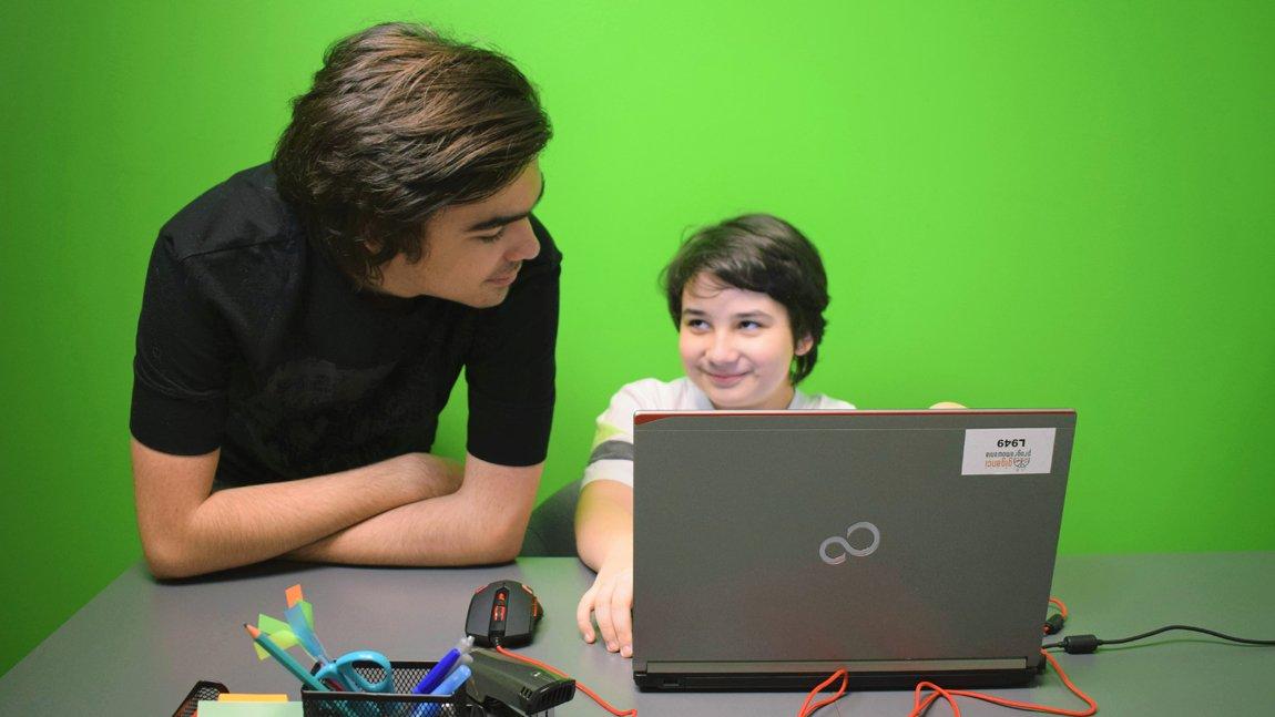 Zdjęcie przedstawiające dwóch chłopaków: starszy pochyla się nad młodszym siedzącym za laptopem