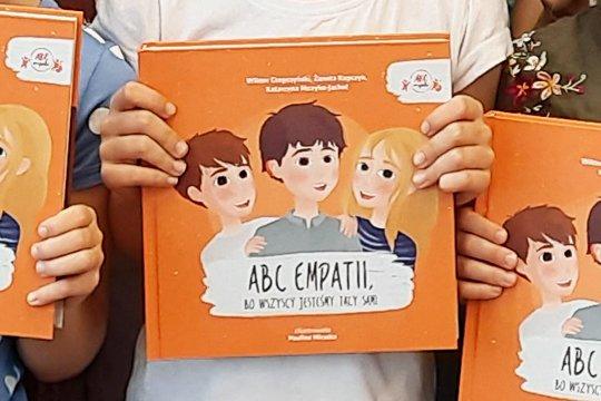 Ksiazka ABC Empatii trzymana w rękach dziecka